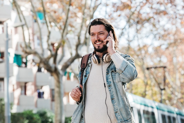 Smiling young man with his backpack talking on mobile phone at outdoors Free Photo