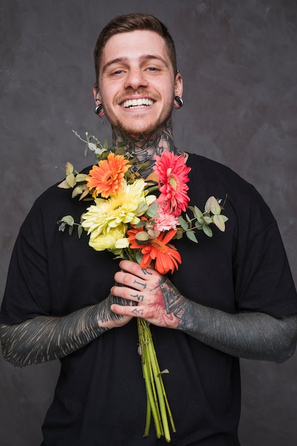 Smiling young man with pierced ears and nose holding bouquet in hand looking at camera Free Photo
