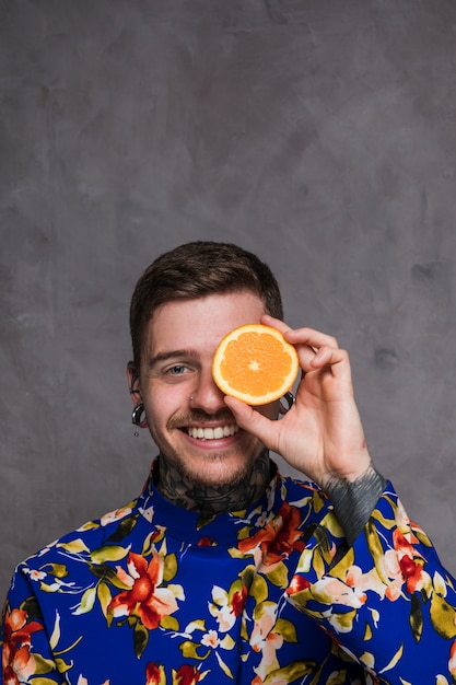 A smiling young man with piercing in the ears and nose holding slice of orange in front of his eyes against grey background Free Photo
