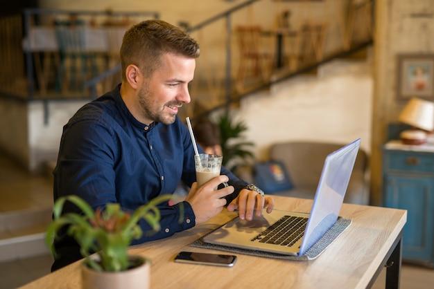 Улыбающийся молодой человек, работающий за компьютером в уютном кафе-баре-ресторане Бесплатные Фотографии