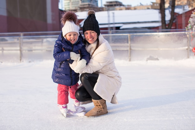 Smiling young mother and her cute little daughter ice skating together Premium Photo