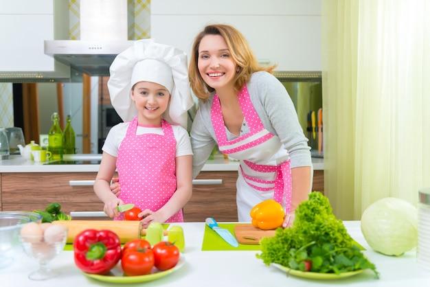 Улыбается молодая мать с дочерью в розовой фартуке, готовя овощи на кухне. Бесплатные Фотографии