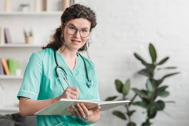 Smiling young nurse with book and pen in the clinic Free Photo