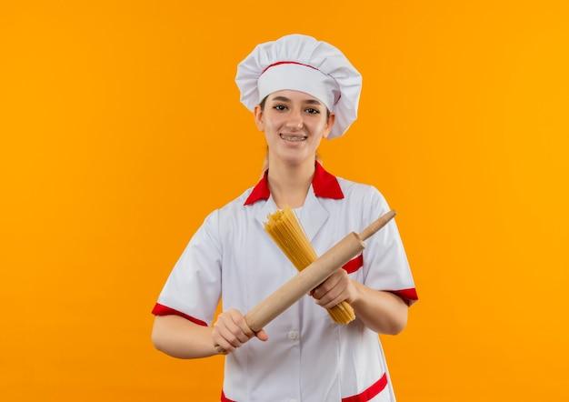 Улыбающийся молодой симпатичный повар в униформе шеф-повара с зубными скобами, держащий макароны спагетти и скалку, изолированные на оранжевом пространстве Бесплатные Фотографии
