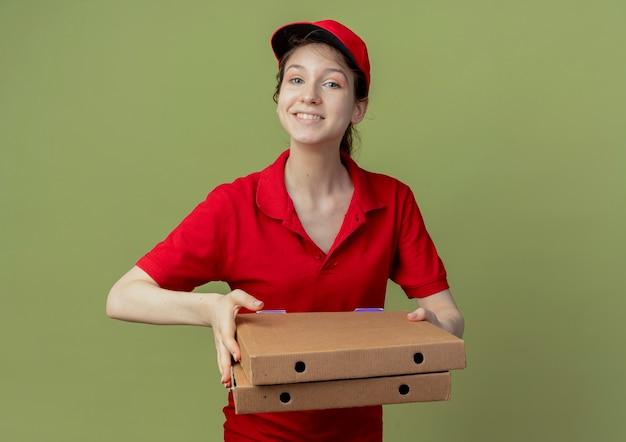 赤い制服とピザのパッケージを保持しているキャップで笑顔の若いかわいい配達の女の子 無料写真
