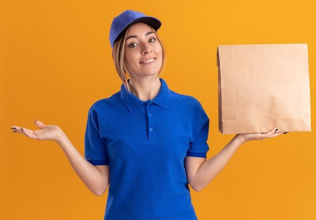 La giovane donna graziosa sorridente di consegna in uniforme tiene la mano aperta e tiene il pacchetto di carta isolato Foto Gratuite