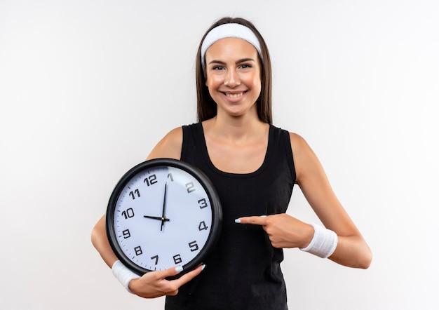 Sorridente giovane ragazza abbastanza sportiva che indossa la fascia e il braccialetto che tiene e che indica l'orologio su uno spazio bianco Foto Gratuite