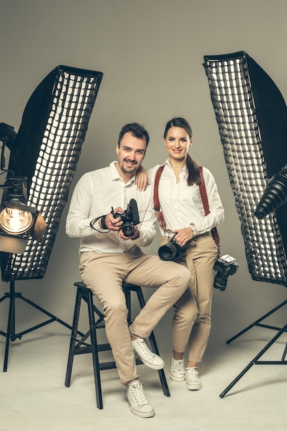 Smiling young professional photographers posing in the studio Premium Photo