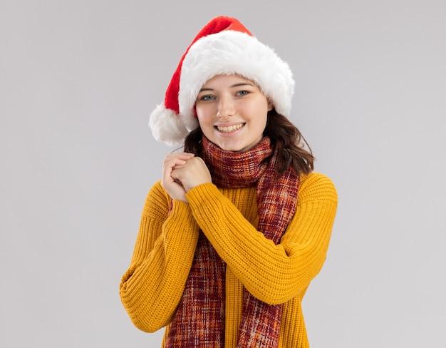 サンタの帽子と首にスカーフを持って笑顔の若いスラブの女の子は手をつないで見える 無料写真