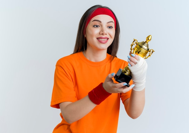 부상당한 손목으로 머리띠와 팔찌를 착용하고 붕대를 감싸고 복사 공간이 흰 벽에 고립 된 우승자 컵을보고 웃는 젊은 스포티 한 여자 무료 사진