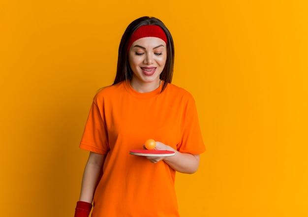 Sorridente giovane donna sportiva che indossa la fascia e braccialetti tenendo e guardando la racchetta da ping pong con pallina da ping pong su di esso Foto Gratuite