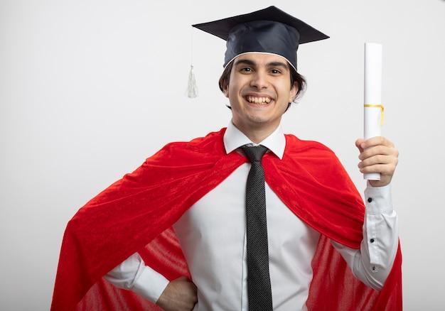 Ragazzo giovane supereroe sorridente che indossa cravatta e cappello laureato che tiene il diploma e che mette la mano sull'anca Foto Gratuite