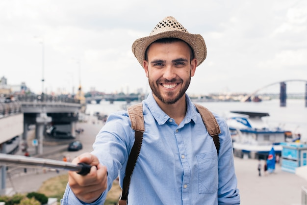 Smiling young traveler wearing hat and taking selfie at outdoors Free Photo