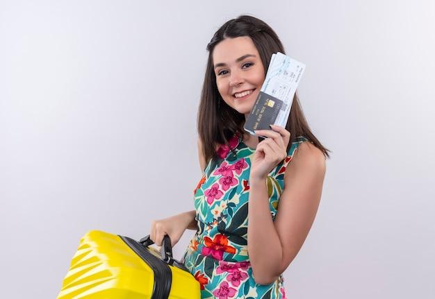 Donna sorridente del giovane viaggiatore che indossa un vestito multicolore che tiene una borsa mobile e biglietti sulla parete bianca Foto Gratuite