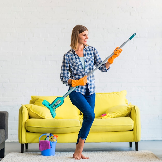 Smiling young woman acting like playing guitar in the living room Free Photo