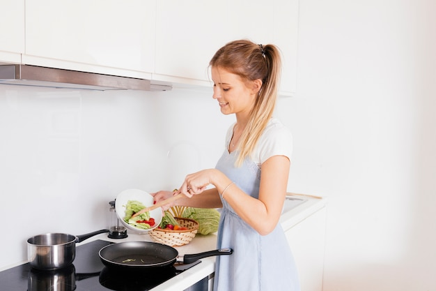 Smiling young woman cooking the vegetables in the kitchen Free Photo