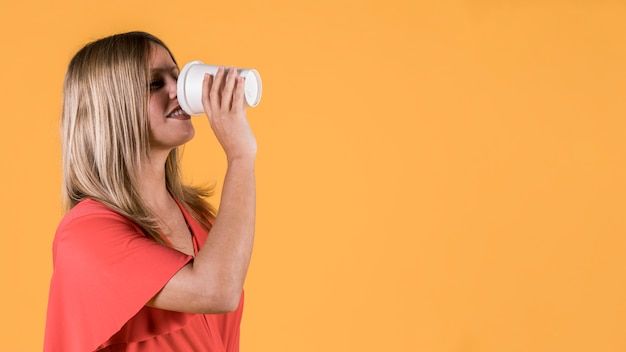 Smiling young woman drinking juice in disposable glass over yellow backdrop Free Photo
