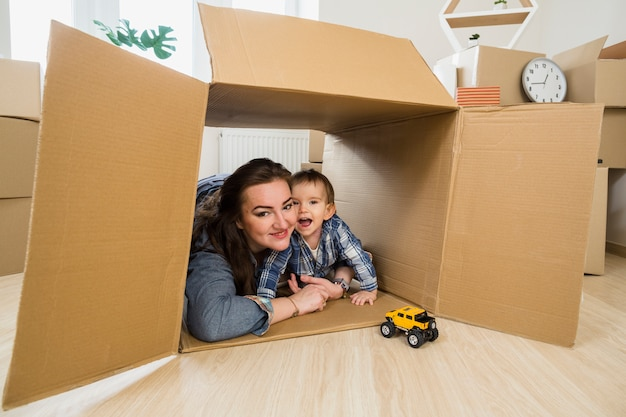 Улыбается молодая женщина, обнимая своего маленького сына в движущейся картонной коробке Бесплатные Фотографии