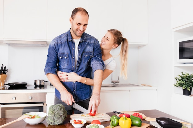 Smiling young woman embracing his husband from behind cutting the vegetable with knife Free Photo