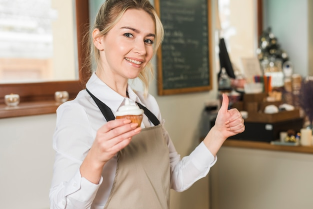 Smiling young woman holding baked muffins in hand showing thumb up sign Free Photo