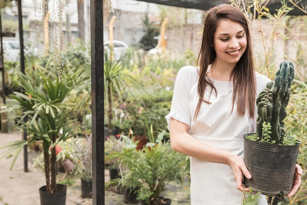 Smiling young woman holding cactus potted plant in greenhouse Free Photo
