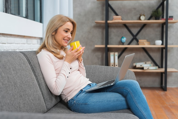 Smiling young woman holding cup of coffee looking at laptop Free Photo