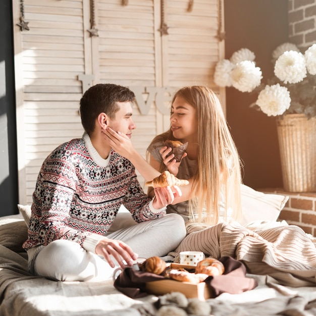 Smiling young woman holding cupcake loving her boyfriend holding croissant Free Photo