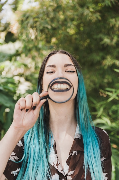 Smiling young woman holding magnifying glass over her face Free Photo