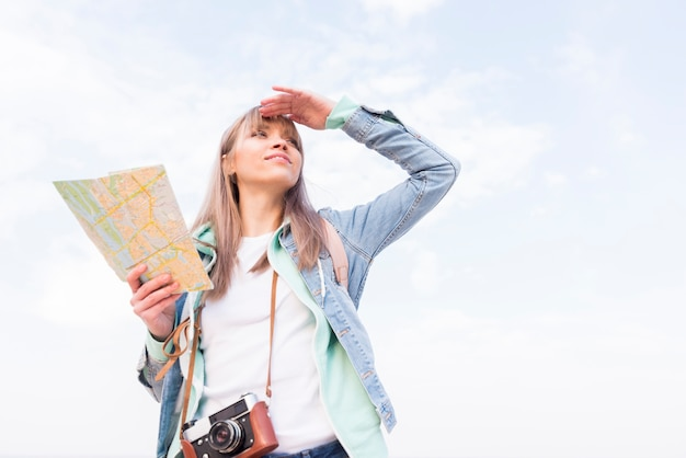 Smiling young woman holding map in hand shielding her eyes Free Photo