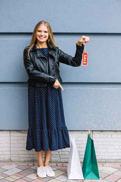 Smiling young woman holding sale tag in hand pointing finger at shopping bags Free Photo