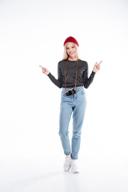 Улыбается молодая женщина в шляпе, стоя и указывая двумя пальцами вверх Бесплатные Фотографии