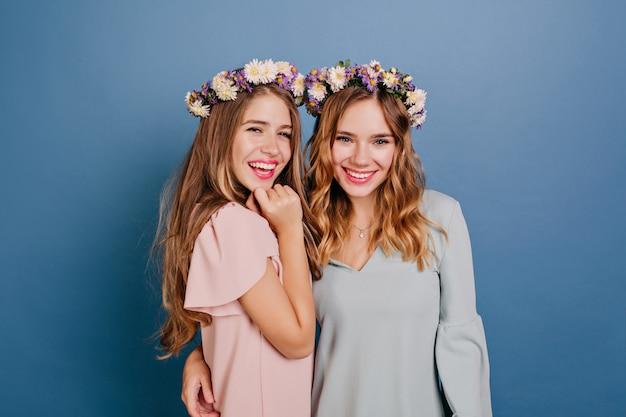 青い壁に彼女の妹を抱きしめて花輪で若い女性の笑顔 無料写真
