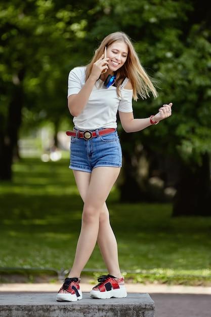 웃는 젊은 여자는 공공 공원에서 휴대 전화를 사용하고 있습니다. 프리미엄 사진