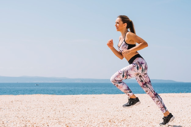 Smiling young woman jogging near the beach against blue sky Free Photo