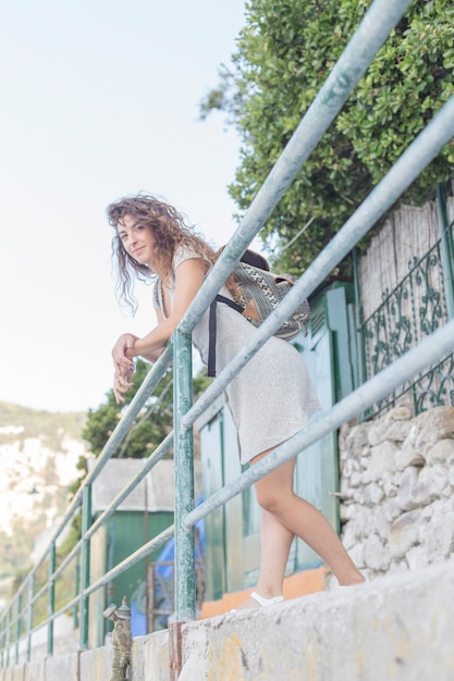 smiling young woman leaning on railing with her backpack photo