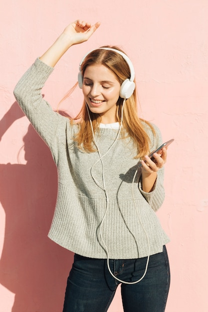 Smiling young woman listening music on headphone dancing against pink wall Free Photo