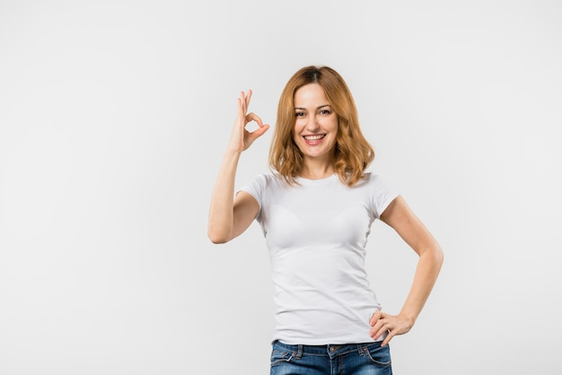 Smiling young woman making ok gesture against white backdrop Free Photo
