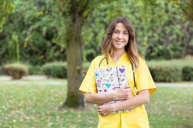 彼女の手にハートのフォルダーを持つ笑顔の若い女性看護師 Premium写真