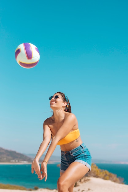 Smiling young woman playing volleyball on beach Free Photo