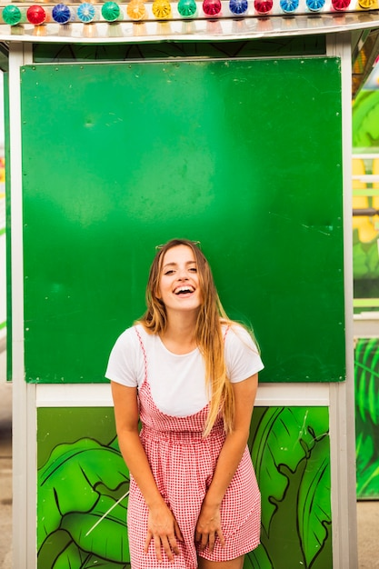 Smiling young woman posing in front of green wall at amusement park Free Photo