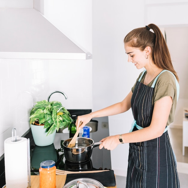 Smiling young woman preparing food in the sauce pan on electric stove Free Photo