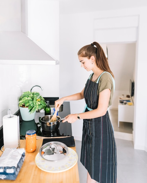 Smiling young woman preparing food in the sauces pan on electric stove Free Photo