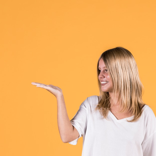 Smiling young woman presenting gesture sign on colored background Free Photo