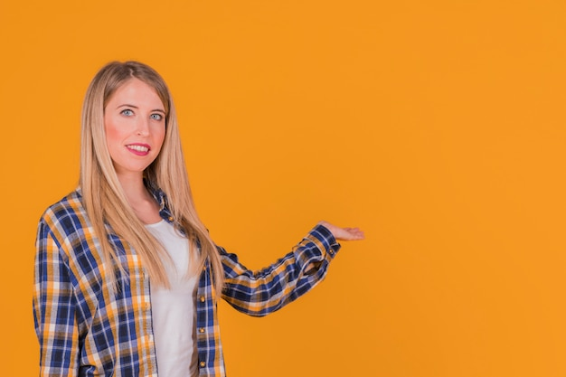 Smiling a young woman presenting something against an orange backdrop Free Photo