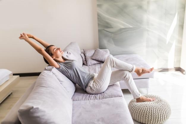 웃는 젊은 여자는 소파에 누워 휴식 무료 사진