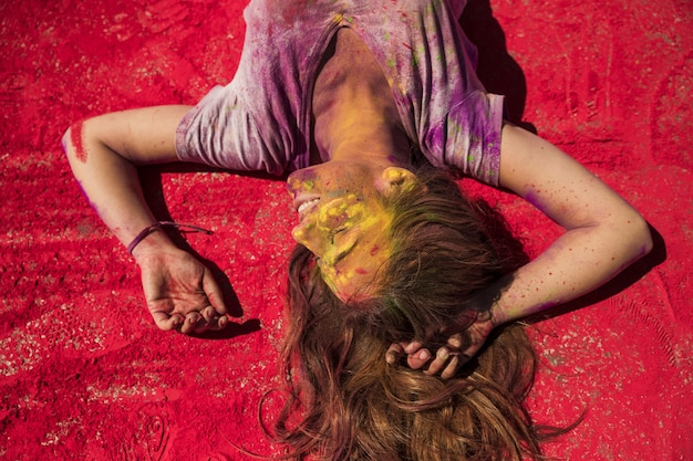 Smiling young woman relaxing on red holi color powder Free Photo