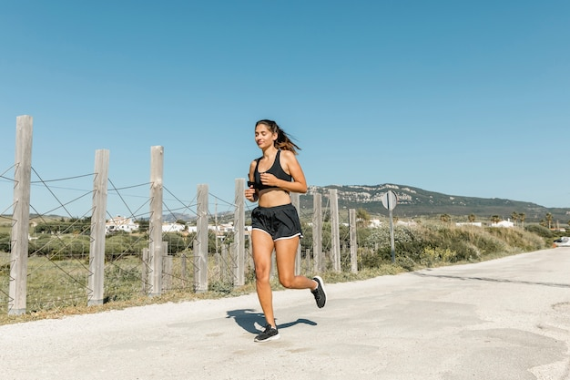 Smiling young woman running along road Free Photo