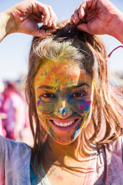 Smiling young woman's face covered with holi color looking at camera Free Photo