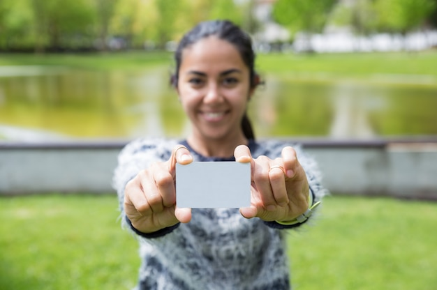 Smiling young woman showing blank plastic card in city park Free Photo