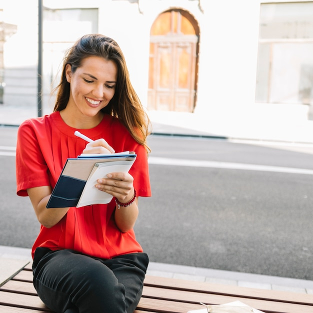Smiling young woman sitting on bench writing note in diary Free Photo